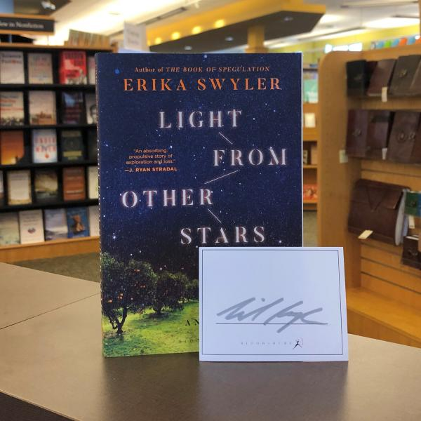 A paperback copy of Light From Other Stars by Erika Swlyer is posed with a signed bookplate
