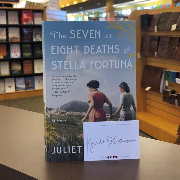 A paperback copy of The Seven or Eight Deaths of Stella Fortuna is posed with a signed bookplate