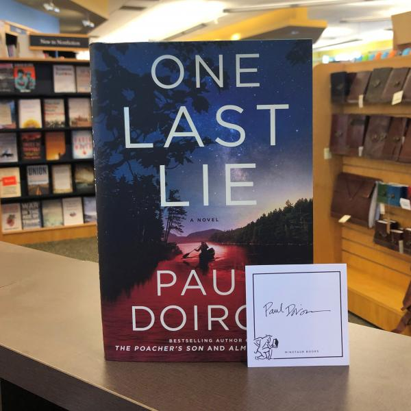 A hardcover copy of One Last Lie by Paul Doiron is posed with a Minotaur Books publisher bookplate signed by Paul Doiron