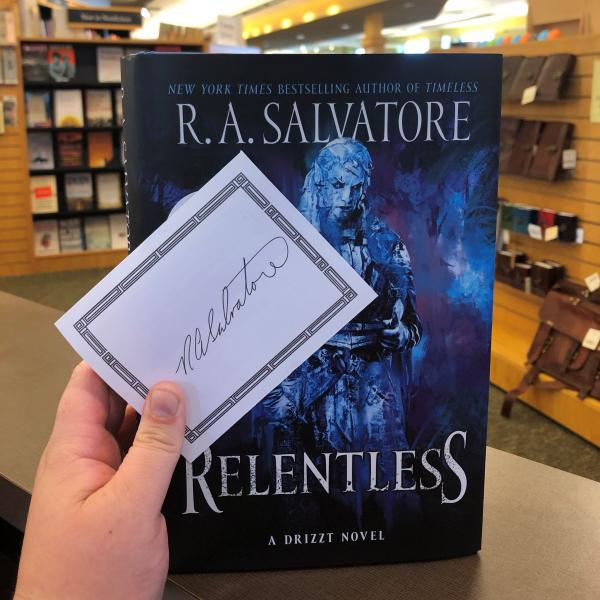 A hardcover copy of Relentless by R A Salvatore is posed with a signed bookplate