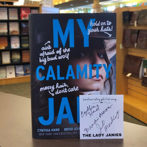 A hardcover copy of My Calamity Jane by The Lady Janies is posed with book plate signed by all three authors