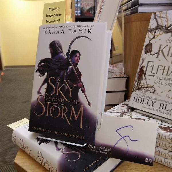 Hardcover copy of A Sky Beyond the Storm by Sabaa Tahir is posed with signed bookplates
